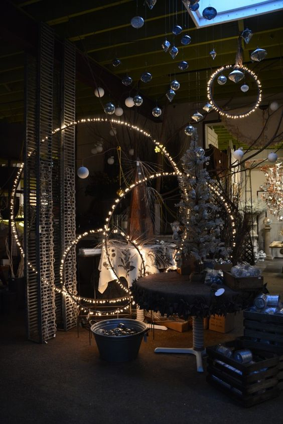 Spray paint hula hoops black, string lights on them and hang them from the ceiling at different heights #design: