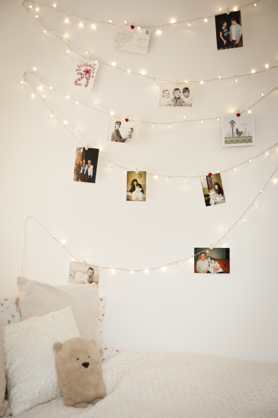 Use warm white fairy lights and picture hooks to create a bedroom photo wall.  #christmaslights #twinklelights