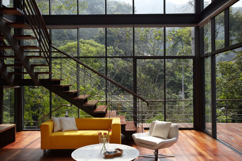 Living room with floor to ceiling glass windows 10 Modern Rooms with a Forest View