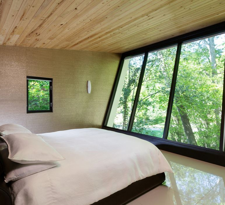 Modern bedroom with slanted windows and a forest view