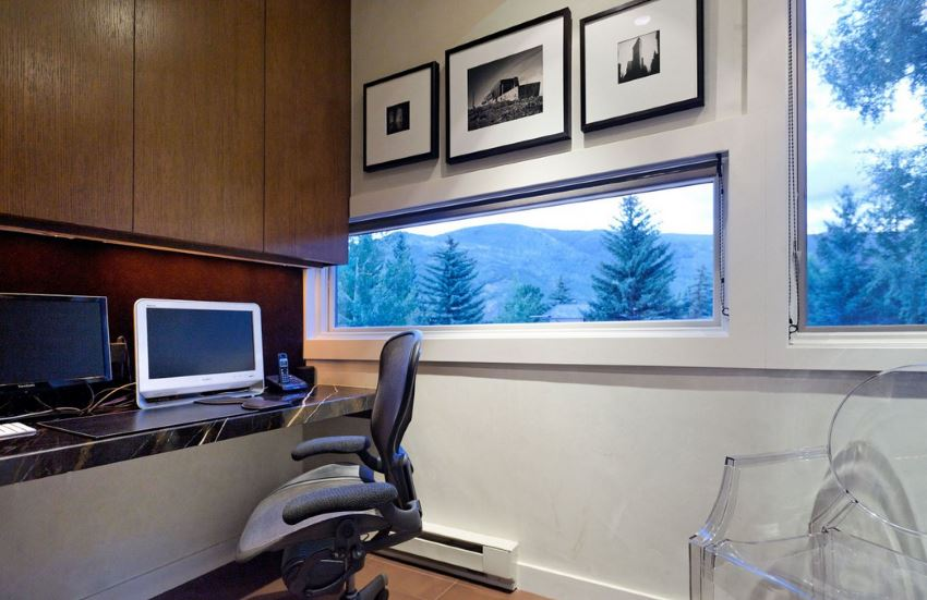 Modern home office with a wooded view