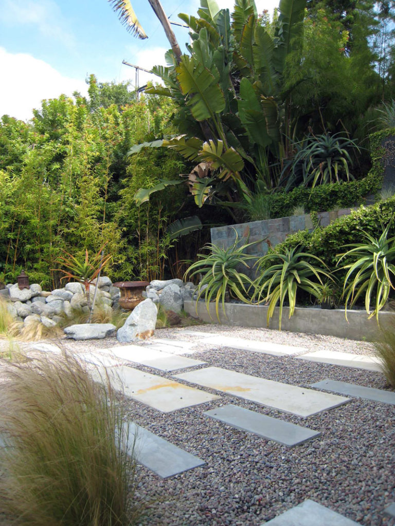 11 Inspirational Rock Gardens To Get You Planning Your Garden // Pavers of various sizes have been placed throughout the yard, and the low maintenance plants and grasses create depth and texture.