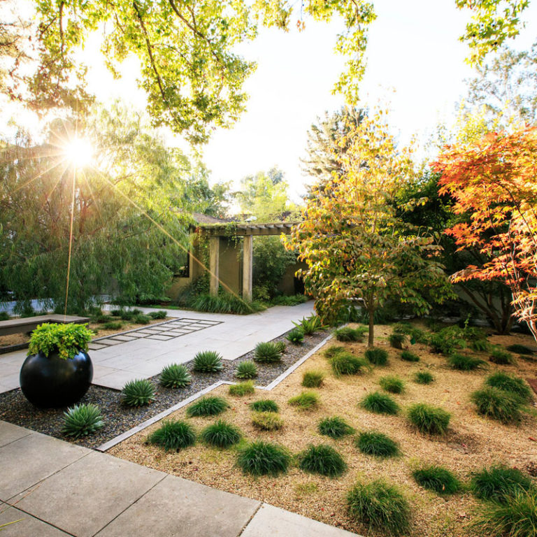 11 Inspirational Rock Gardens To Get You Planning Your Garden // This yard uses drought tolerant plants and small stones of various kinds to create a low maintenance yard full of color and texture.