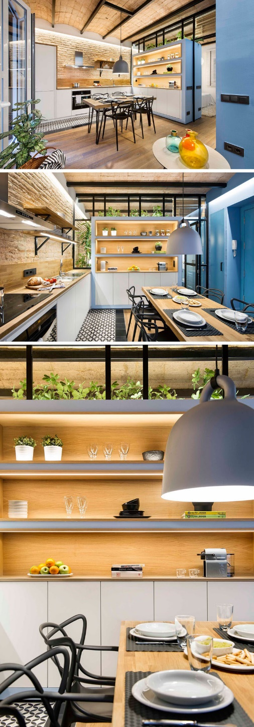 In this small apartment kitchen, built-in wood-lined shelves with hidden lighting provide much needed storage space. #shelving #BuiltInShelving #WoodLinedShelving #WoodLinedBookshelf #Kitchen