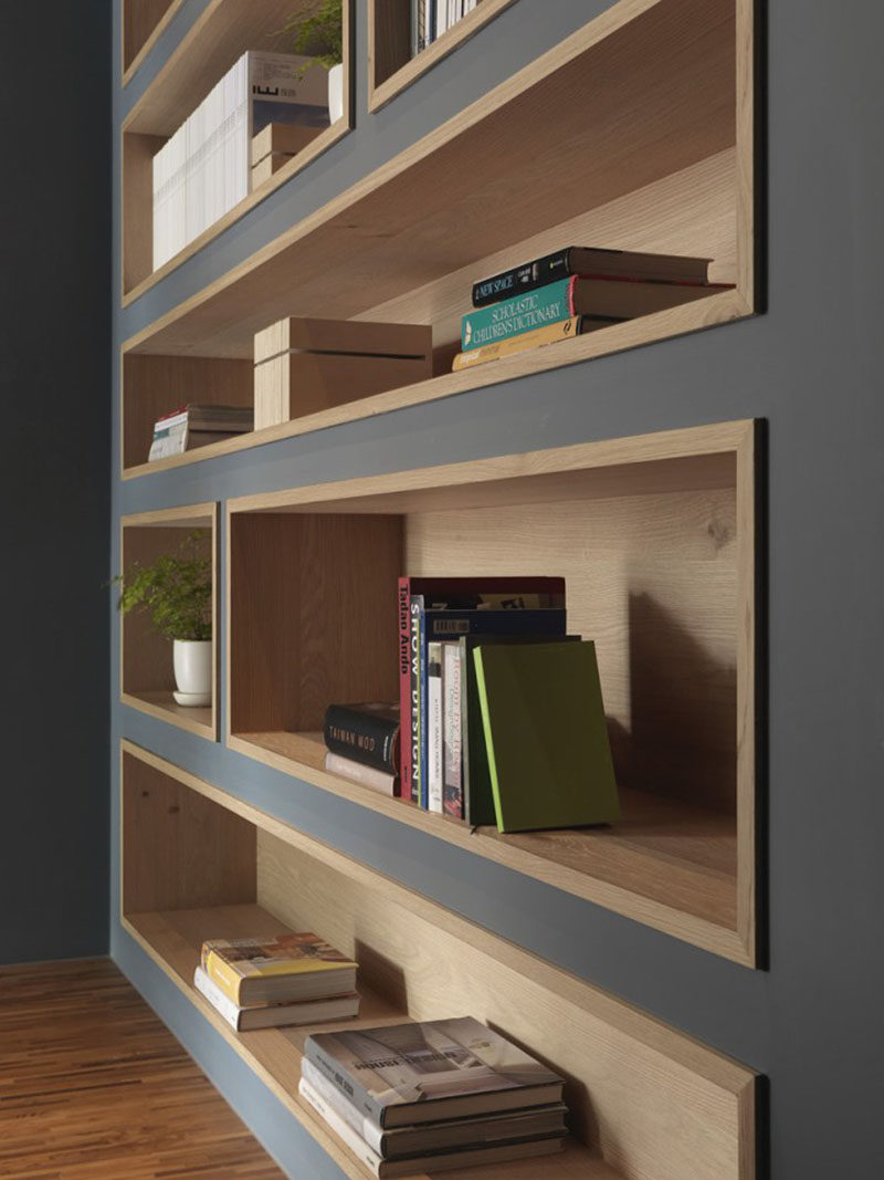 To make the built-in bookshelves on this deep grey wall stand out, the shelves were lined with wood to add a natural touch in the office interior. #shelving #BuiltInShelving #WoodLinedShelving #WoodLinedBookshelf
