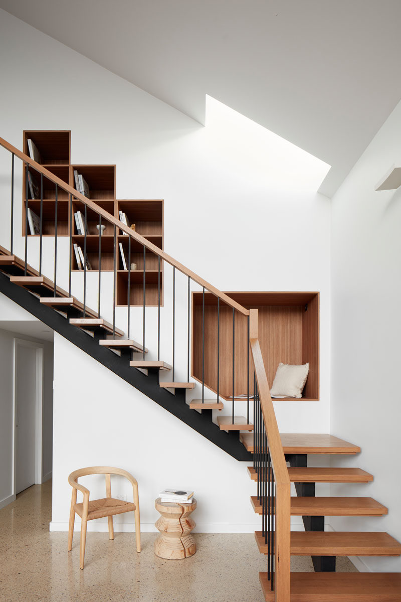 Wood-lined bookshelves and a seating nook have been built into the wall next to this modern staircase. #shelving #BuiltInShelving #WoodLinedShelving