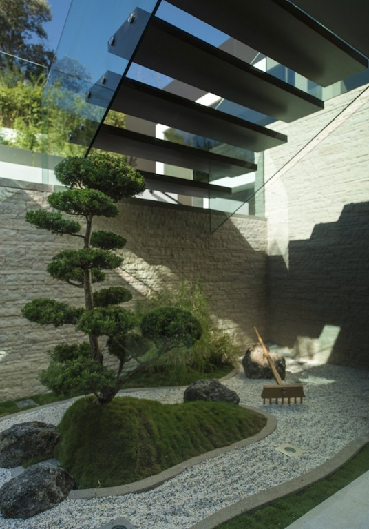 This small zen garden has a small feature in the center with a single tree and some moss covered stone. Zen gardens can have a bit of greenery, but the majority of the garden should be focused on the gravel or sand.