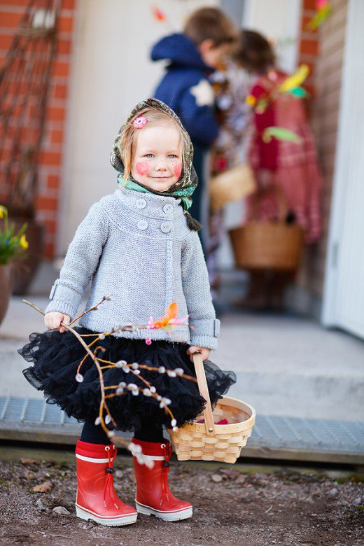 Adorable little girl going around seeking treats as part of the Sweden Easter Tradition